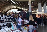 """""""Kanserde Erken Teşhis Hayat Kurtarır"""" sloganı baskılı tişörtler giyen pazar esnafı satış yaparken."""