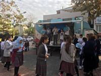 Sağlıklı Yaşam aracından Şehit Deniz Piyade Er Tahsin Şen Ortaokulu öğrencilerine broşür dağıtılıyor.