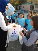 Çocuklara sağlıklı yaşam aracından atkı-bere ve boyama kitabı hediyeleri dağıtılıyor.