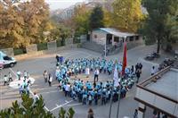 Öğrenciler okul bahçesinde el ele tutuşarak diyabetin sembolü olan mavi halka şekli yapıyor.